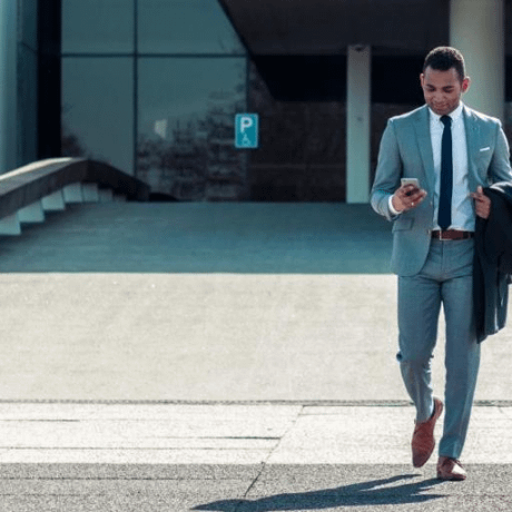 man on a phone walking out of an office checking his intercom anywhere app